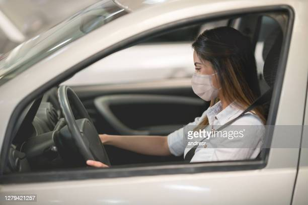 woman wearing a facemask while driving a car at the dealership or the garage - test drive stock pictures, royalty-free photos & images