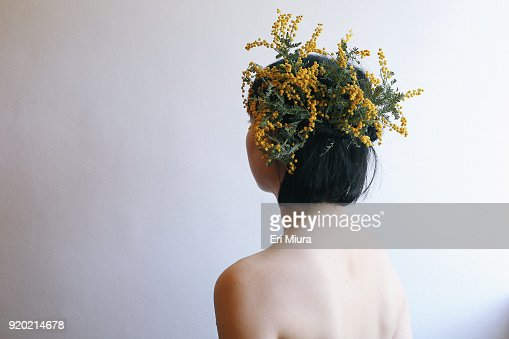 A woman wearing a fancy yellow hat made of flowers