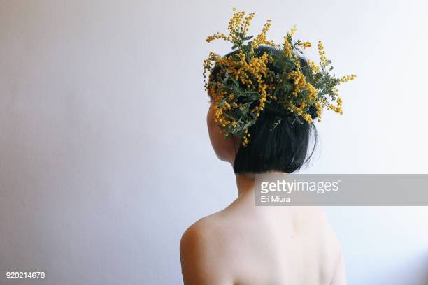 a woman wearing a fancy yellow hat made of flowers - mimosa fiore foto e immagini stock