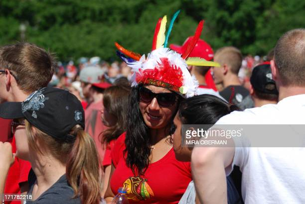 Woman wearing a feather headdress is among tens of thousands of fans who filled the streets of Chicago on June 28, 2013 to cheer on the Blackhawks...
