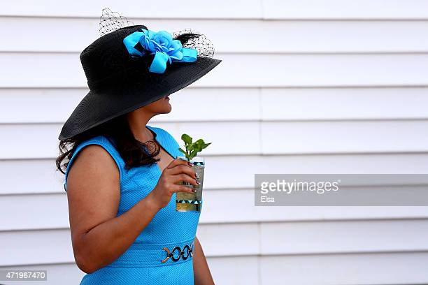 A woman wearing a festive hat and drinking a Mint Julep looks on prior to the 141st running of the Kentucky Derby at Churchill Downs on May 2 2015 in...