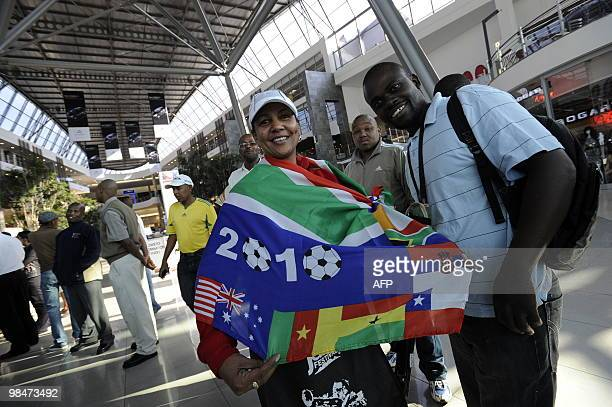 A woman wearing a football supporters flag queues to purchase official 2010 FIFA World Cup tickets on April 15 2010 at the Maponya shopping mall in...