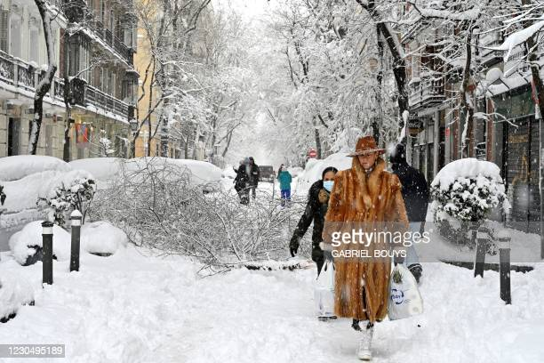 Woman wearing a fur coat walks amid a heavy snowfall in Madrid on January 9, 2021. - Snowstorms across much of Spain left three people dead and...