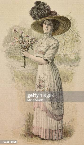 Woman wearing a garden party dress white Crepe de Chine with Pompadour prints pleated skirt corset with high collar and a hat with feathers creation...