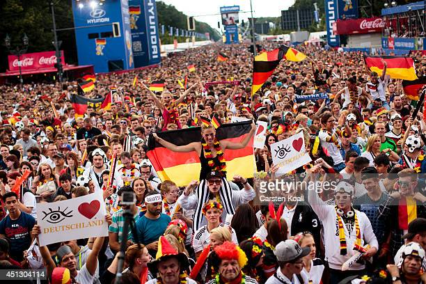 A woman wearing a german national flag sitting on the shoulder of a man surrounded by german fans waving german flags celebrating while they watch...