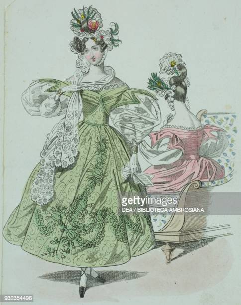 Woman wearing a green dress decorated with plant motifs puffed sleeves with lace and flowers in her hair and a woman wearing a pink dress with puffed...