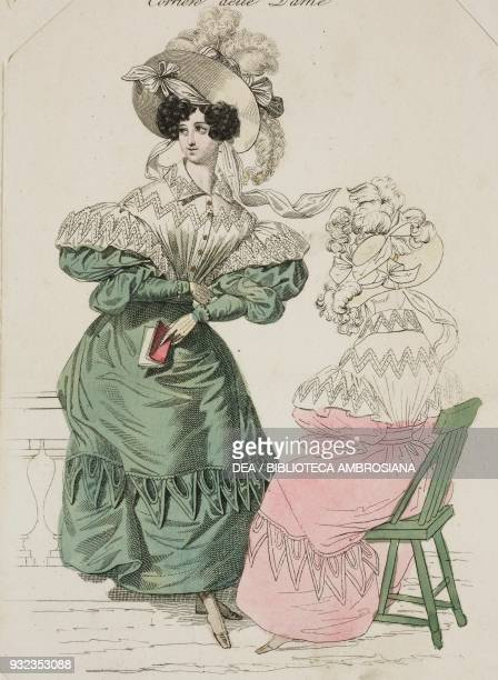 Woman wearing a green dress with puffed sleeves and white blouse with lightcoloured hat adorned with ribbons and feathers and a woman wearing the...