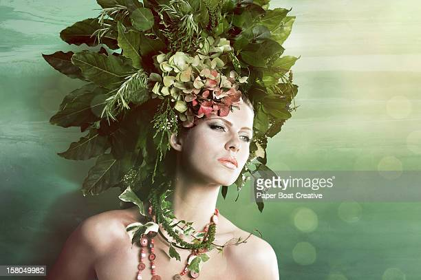 Woman wearing a green hat made of plants