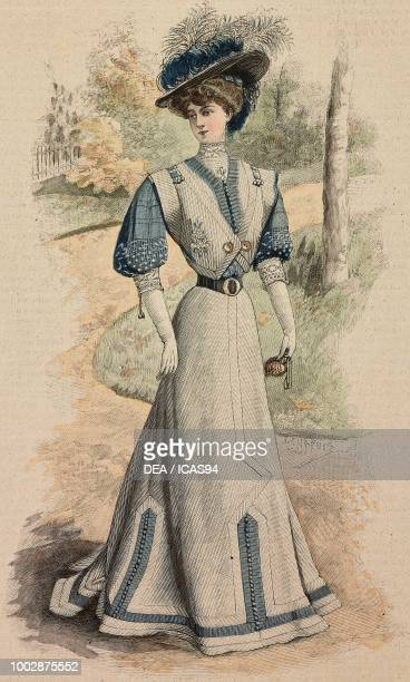 Woman wearing a grey and blue Pekin woolen dress decorated with trimmings silk muslin sleeves and a hat with feathers creation by Martial and Armand...