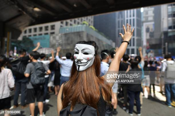 TOPSHOT A woman wearing a Guy Fawkes mask joins people taking part in a protest against a potential government ban on protesters wearing face masks...