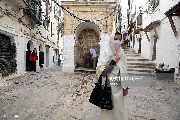 Woman wearing a haik a long white embroidered gown Algerian women's traditional dress walking in a lane of Algiers kasbah