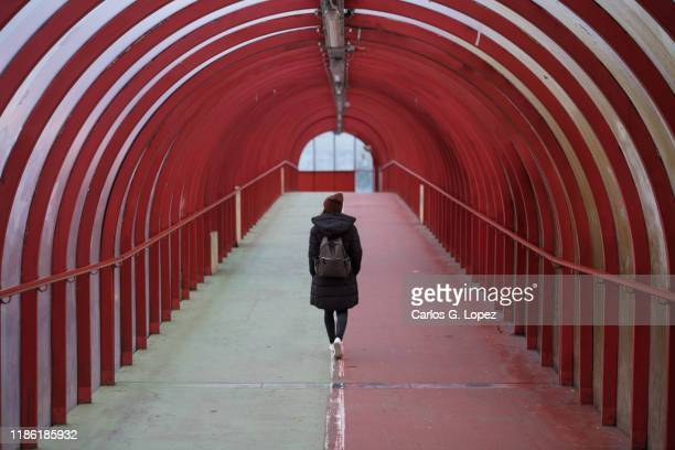 woman wearing a hat and a backpack walks in the middle of a covered walkway bridge over the river clyde in glasgow, scotland, united kingdom - glasgow schottland stock-fotos und bilder