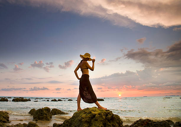 A Woman Wearing A Hat And Sarong Stands On The Beach Of A Tropical Island At Sunset Wall Art