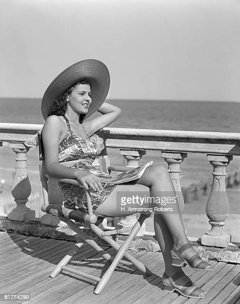 Woman wearing a hat, posing at the beach.