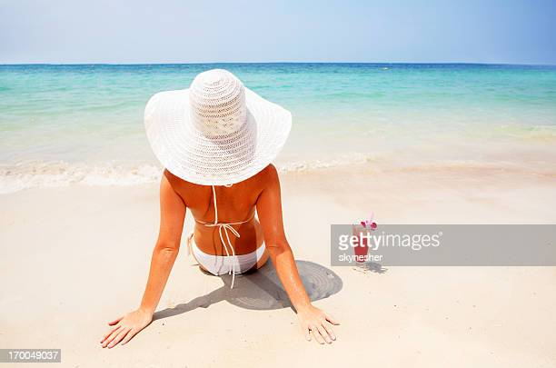 Woman wearing a hat relaxing on the beach.