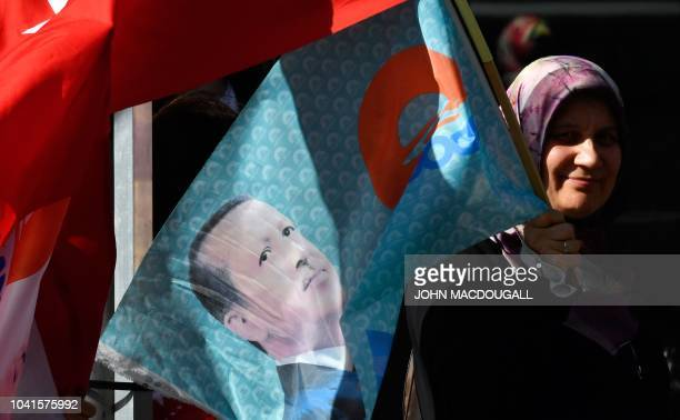 A woman wearing a headscarf holds a flag with the portrait of Turkish President Recep Tayyip Erdogan on September 27 2018 near the Adlon Hotel close...