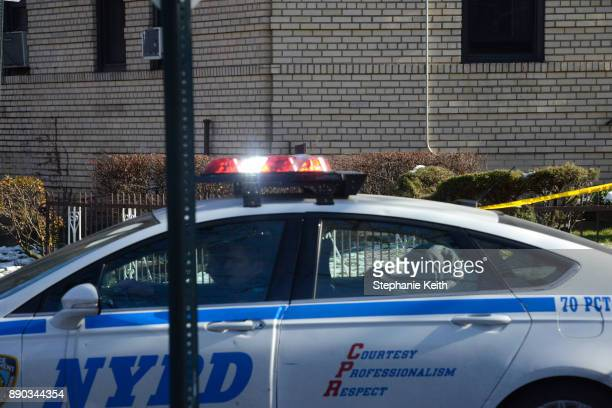 A woman wearing a headscarf is driven away in a police car by members of the New York City Police Department outside a Brooklyn address on Ocean...