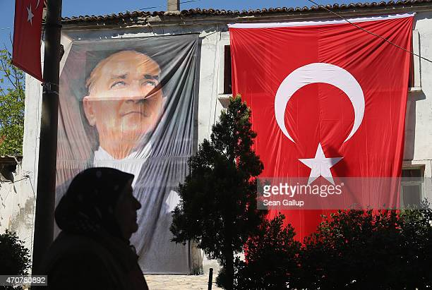 A woman wearing a headscarf walks past a portrait of Turkish Gallipoli division commander and founder of the first Turkish Republic Mustafa Kemal...