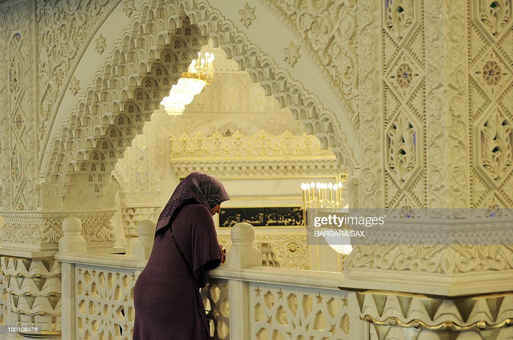 A woman wearing a headscarf watches from a gallery of the new Omar Mosque in Berlin's Kreuzberg district during the inauguration of the Islamic Maschari Centre on May 21, 2010. The centre includes the mosque, a kindergarden, a school, a library, a travel agency and a shopping centre.