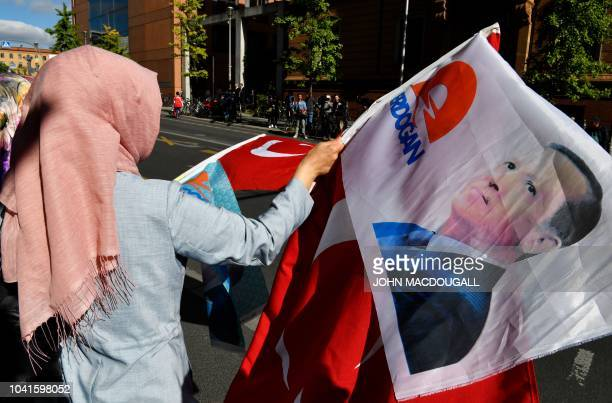 A woman wearing a headscarf waves with a flag with the portrait of Turkish President Recep Tayyip Erdogan on September 27 2018 near the Adlon Hotel...