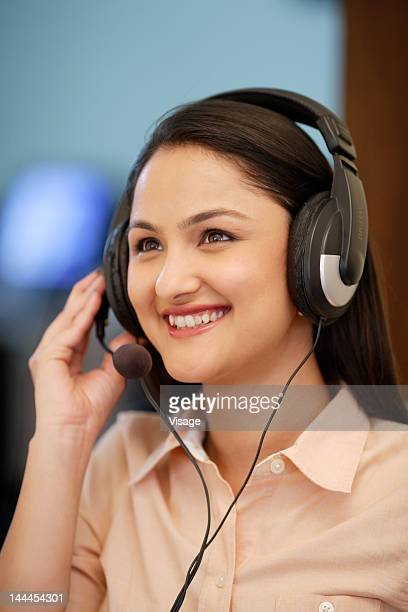 A woman wearing a headset and smiling, selective focus