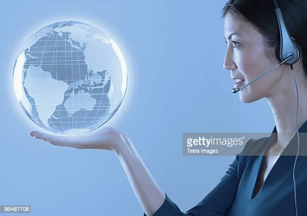 Woman wearing a headset holding a globe