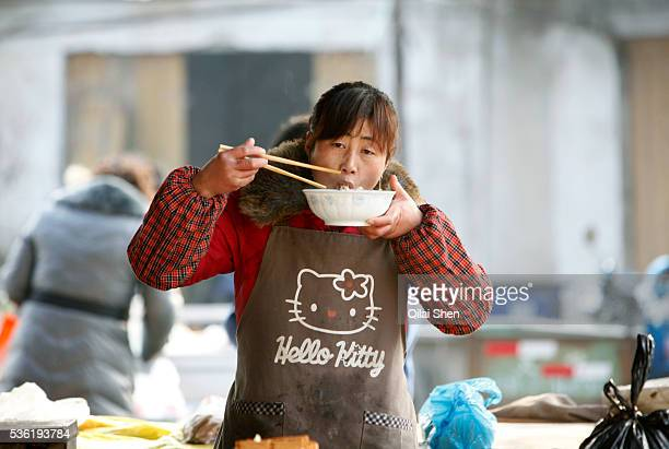 A woman wearing a Hello Kitty apron eats a bowl of noodles at a market in Zhujiao Township Chuzhou Anhui Province China on 02 March 2011 Chuzhou is...