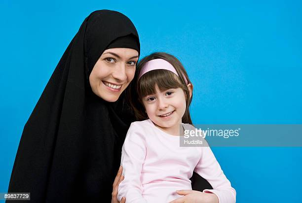 A woman wearing a Hijab and holding her daughter on her lap