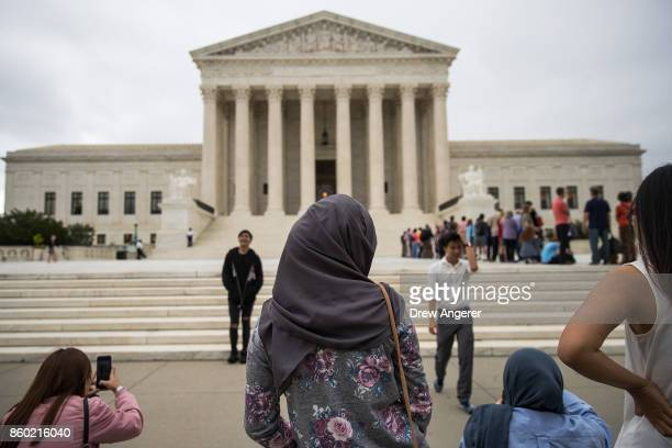 A woman wearing a hijab stands outside the US Supreme Court October 11 2017 in Washington DC On Tuesday the US Supreme Court dismissed one of two...