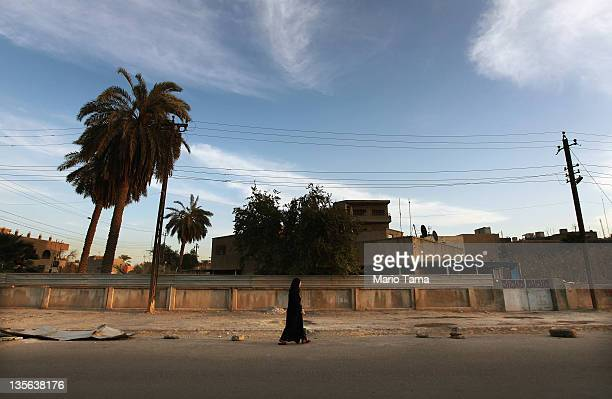 A woman wearing a hijab walks down a street on December 12 2011 in Baghdad Iraq Iraq is transitioning nearly nine years after the 2003 US invasion...