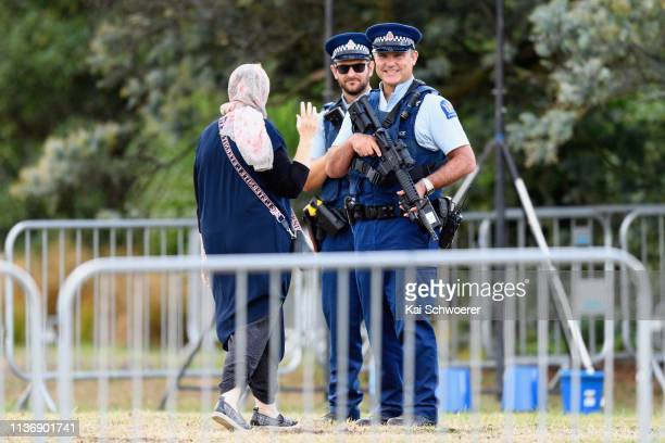 A woman wearing a hijab walks greets armed police officers prior to the first burials of victims at Memorial Park Cemetery on March 20 2019 in...