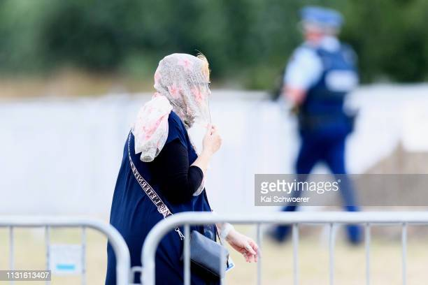 A woman wearing a hijab walks past armed police officers prior to the first burials of victims at Memorial Park Cemetery on March 20 2019 in...
