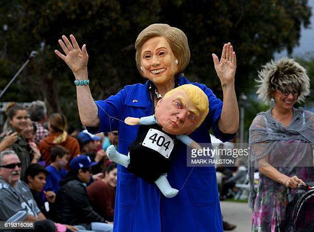 A woman wearing a Hillary Clinton mask carries a Republican presidential nominee Donald Trump doll during a Halloween parade in Long Beach California...