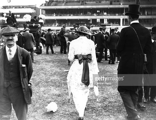A woman wearing a hobble skirt with a large bowtied jacket at Ascot