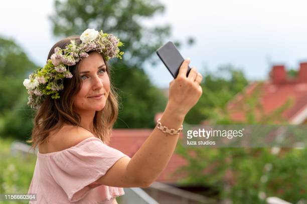 woman wearing a homemade flower crown on midsummer in sweden - midsummer sweden stock pictures, royalty-free photos & images
