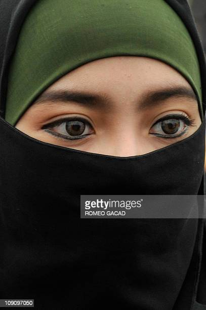 A woman wearing a jilbab attends mass prayers at the National Monument park in Jakarta marking the birth of Islam's Prophet Mohammad on February 15...