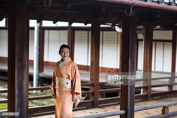 Woman wearing a kimono walking through a temple.