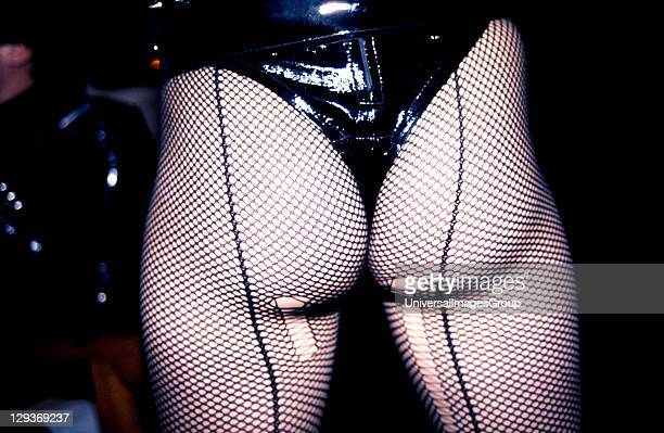 Woman wearing a leather thong and laddered fish net tights, UK, 1980's