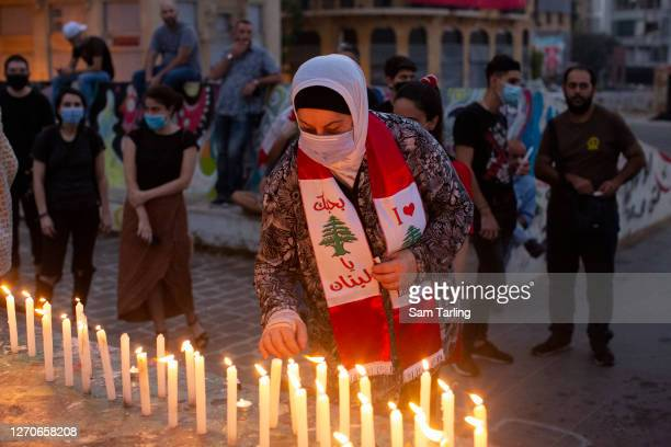 Woman wearing a Lebanese flag-themed scarf lights a candle at a vigil to mark one month since the huge explosion in Beirut port, on September 4, 2020...