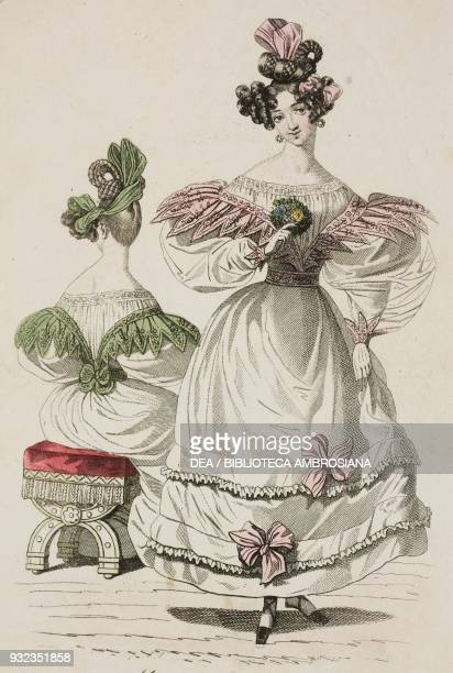 Woman wearing a lightcoloured dress with puffed sleeves decorative inserts and pink bows which are picked up in her hairstyle and a woman wearing the...