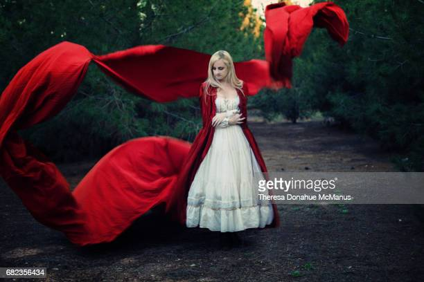 woman wearing a long flowing red cape - flowing cape stock pictures, royalty-free photos & images