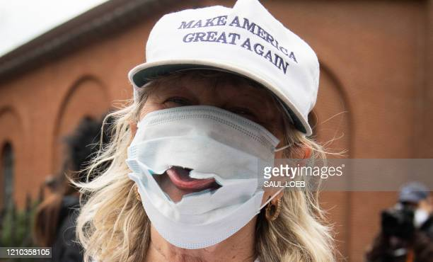 TOPSHOT A woman wearing a Make America Great Again hat sticks her tongue out of a damaged mask as demonstrators protest during a Reopen Maryland...