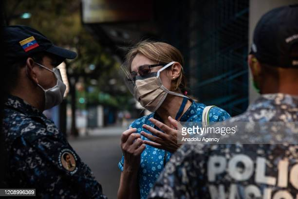 A woman wearing a makeshift screen mask talks with Bolivarian National Police in empty Chacao Subway Station as a preventive measure against the new...
