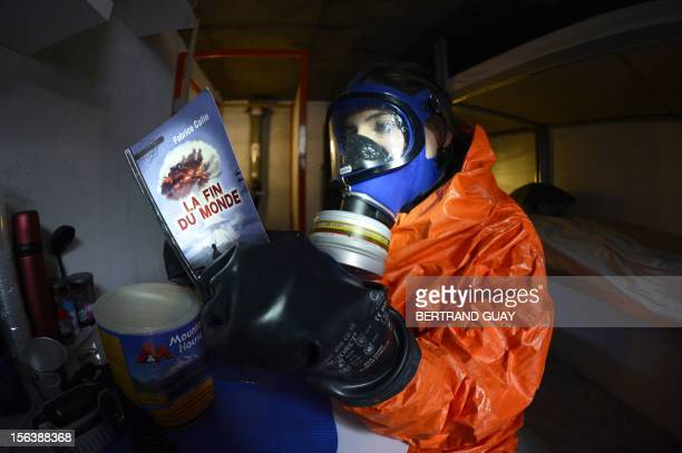 A woman wearing a mask and gloves reads a book entitled 'The end of the world' by French writer Fabrice Collin in a nuclear shelter displayed in...