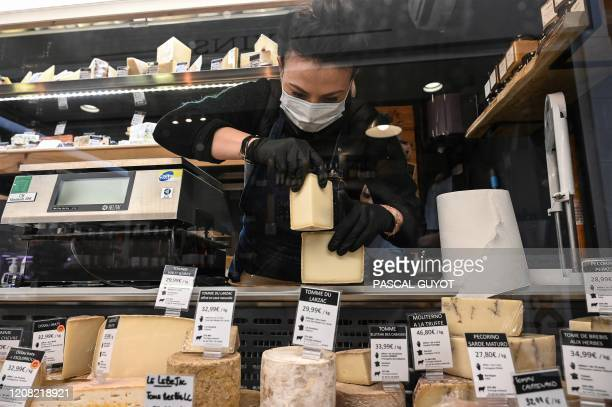 Woman wearing a mask and gloves sets up her display stand in a cheese store in the center of Montpellier, on March 25 as the country is under...