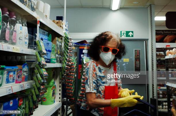 Woman wearing a mask and kitchen gloves shops in a branch of supermarket chain Sainsbury's in the Bayswater district of London, England, on May 13,...