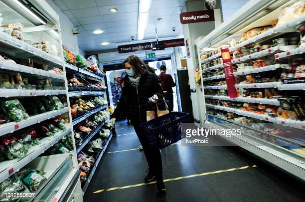 Woman wearing a mask and latex gloves shops in a branch of supermarket chain Sainsbury's, stepping over social distancing markers subdividing the...