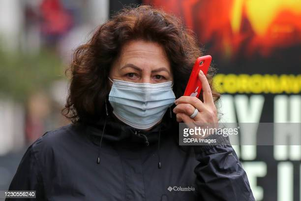 Woman wearing a mask as a preventive measure against the spread of covid-19 talks on a mobile phone while walking along the Street in London. Over...