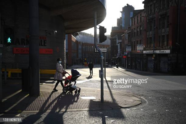 Woman wearing a mask because of the coronavirus pandemic pushes a pram in central Manchester, northwest England, on March 25, 2021 as life continues...