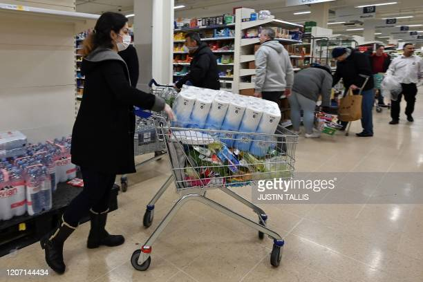 Woman wearing a mask buys toilet paper at a supermarket in London on March 14 as consumers worry about product shortages, leading to the stockpiling...